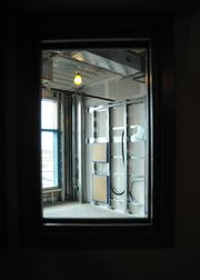 A view of a patient room through the observation window at a nurse's station