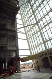 Construction progresses behind the windows of the main entrance to the inpatient facility.
