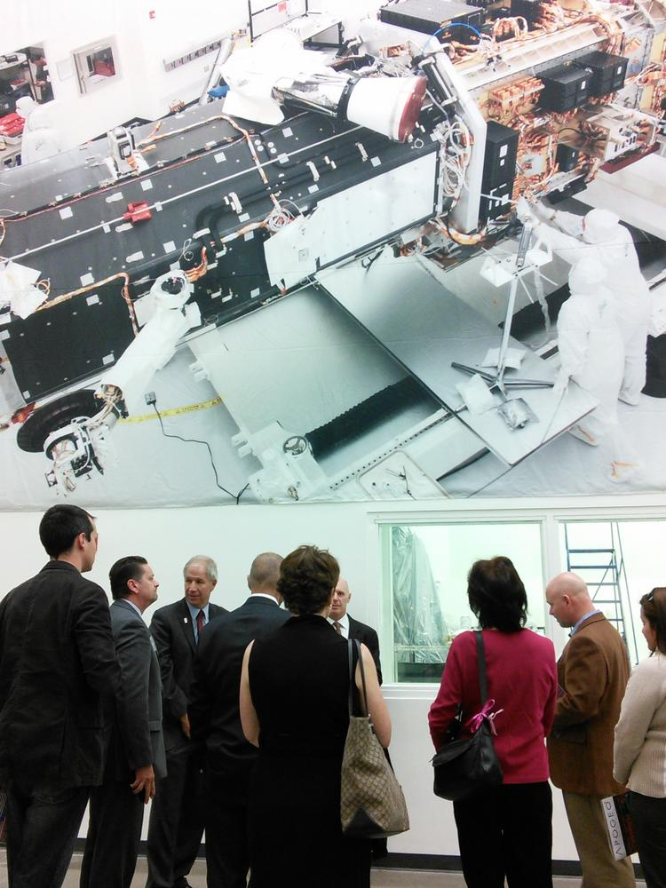 Guests gather near a viewing window at Ball Aerospace's manufacturing plant in Boulder on May 13 beneath a large photograph of the WorldView-3 satellite built by Ball for Longmont-based space imaging company DigitalGlobe Inc.