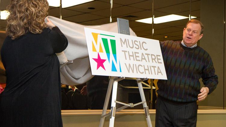 Darcee Datteeri, president-elect of the Board of Directors for Music Theatre Wichita, and Wayne Bryan, producing artistic director of Music Theatre Wichita, unveil their new logo design Thursday morning at Century II.