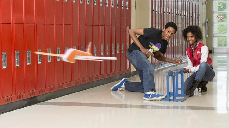Domonique Young helps Bria Williamson launch the glider she built in aviation fundamentals class at Andrews Aviation Academy in High Point.