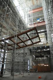 Scaffold surrounds the construction of a grand staircase that will access every floor.