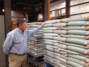 New Earth President Clayton Leonard inspects bags of soil at the company's San Antonio packaging operation.