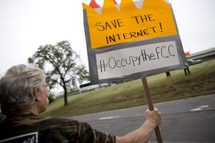 Demonstrator Kenneth Ashe holds a sign in support of net neutrality outside the Federal Communications Commission (FCC) headquarters in Washington, D.C., U.S., on Wednesday, May 14, 2014.