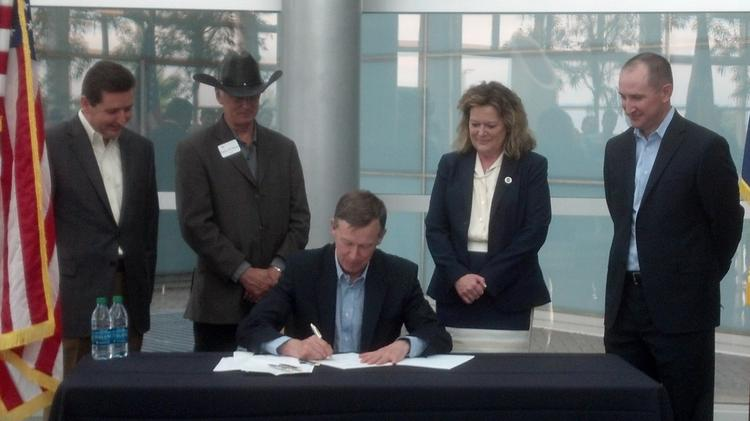 Gov. John Hickenlooper signs House Bill 1014 into law Friday while surrounded by (L to R): Grover Wray, senior vice president of DigitalGlobe Inc.; Westminster Mayor Herb Atchison; state Rep. Tracy Kraft-Tharp; and Dan Jablonsky, DigitalGlobe general counsel