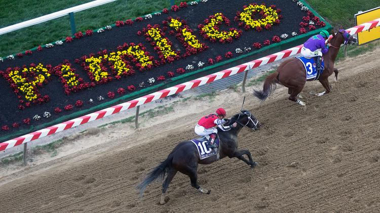 Jockey Victor Espinoza rides California Chrome, the No. 3 horse, to victory in the Preakness Race at Pimlico Race Course. Ride on Curlin, No. 10, finished second.