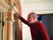 Andy May, an expert in historic home renovations, strips multiple layers of paint from a decorative arch made of cherry hardwood on the first floor of 60 Second St.
