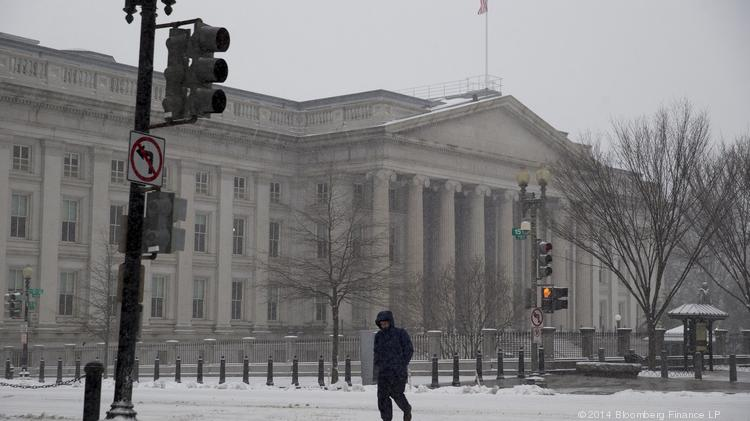 A pedestrian walks across a snow covered street past the U.S. Treasury in Washington, D.C., U.S., on Monday, March 3, 2014. D.C. is considered relatively safe for pedestrians in a new report from Smart Growth America.