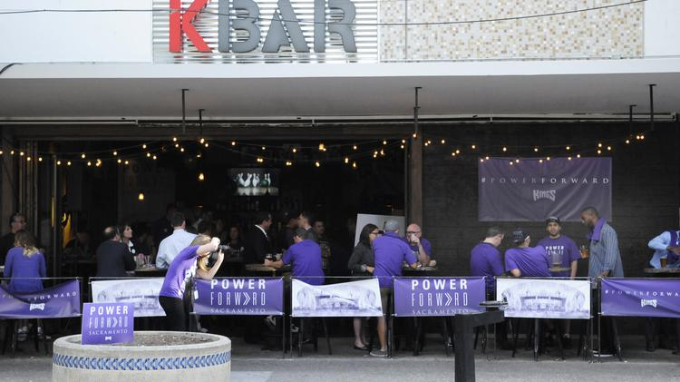 A group of Sacramento Kings fans is photographed at KBAR by a photographer for the team.