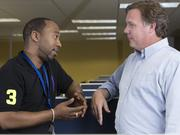 Global Conduit Senior Local Executive Chris Turner, right, talks with supervisor Charles Sanders at the call center.