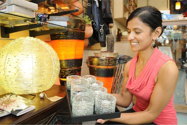 Nandini Bhattacharjee arranges hand-cut candle holders made from recycled glass in her new Kailua boutique, Nomads Hawaii, which she opened about two weeks ago. The candle holders, handmade in Ubud, Indonesia, along with the lamp made from the same materials, are typical of the items from around the world that she sells.