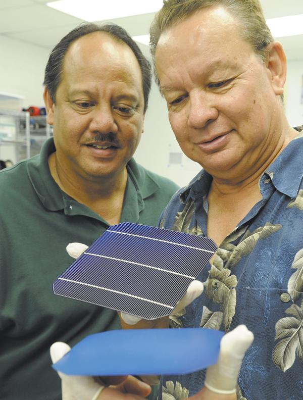 President Briand Achong, left, and Jim Chaney, director of product development, examine solar cells produced by GreenPath Technologies for use in the field.