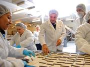 Pascal Rigo (center) helps assemble chocolate croissants at his 70,000-square-foot facility in South San Francisco.