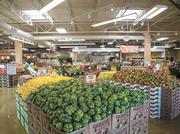 Boxes of green bell peppers and lemons fill the produce section.