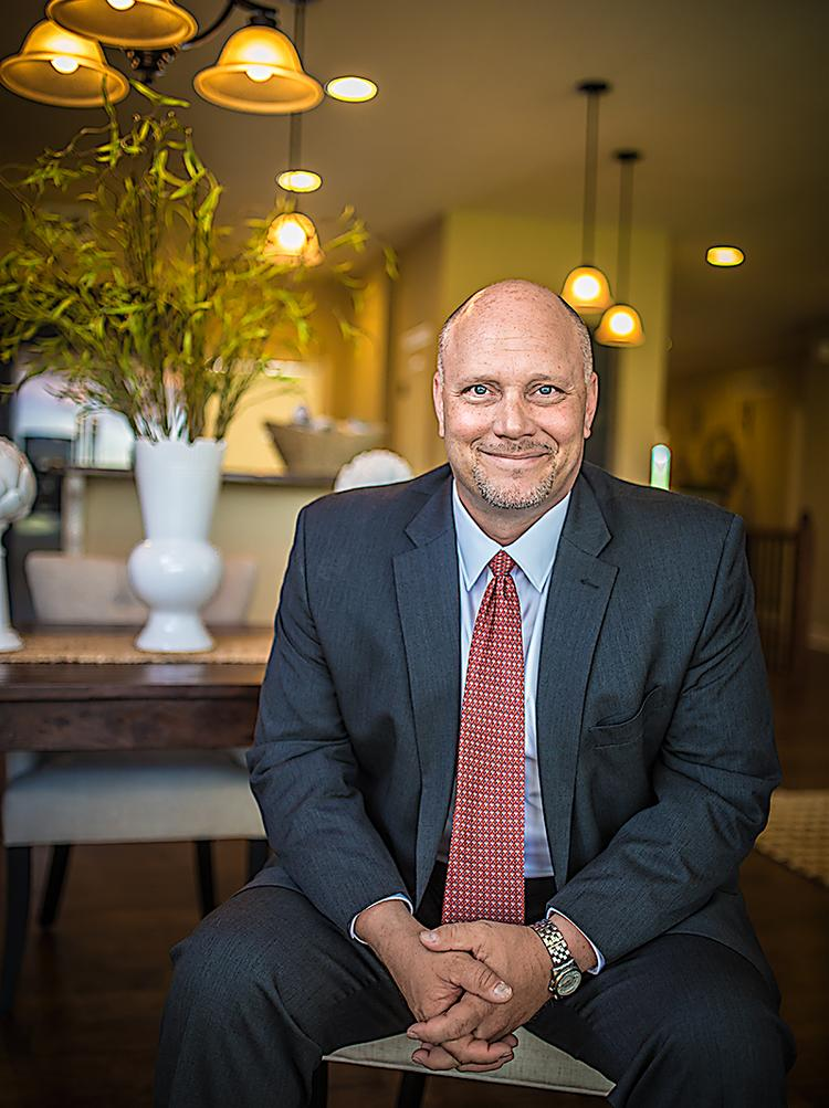 """Mike Brown, division manager of Rausch Coleman Homes, sits inside a model home at 26120 W. 142nd Terrace in Olathe. The house recently won a """"grand award"""" as part of the Spring Parade of Homes' American Dream Awards program."""