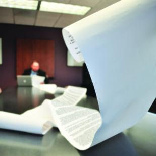 Lawyer Matthew D. Mangum scrolls through printouts of email legal disclaimers