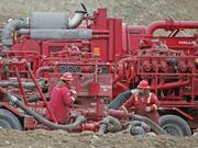 Two Halliburton laborers work at a natural gas drilling site near Rifle.