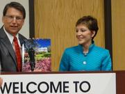 Gov. Pat McCrory presents Reynolds American CEO Susan Cameron with a book about North Carolina at a press conference where Reynolds announced it was adding 200 jobs in Tobaccoville.