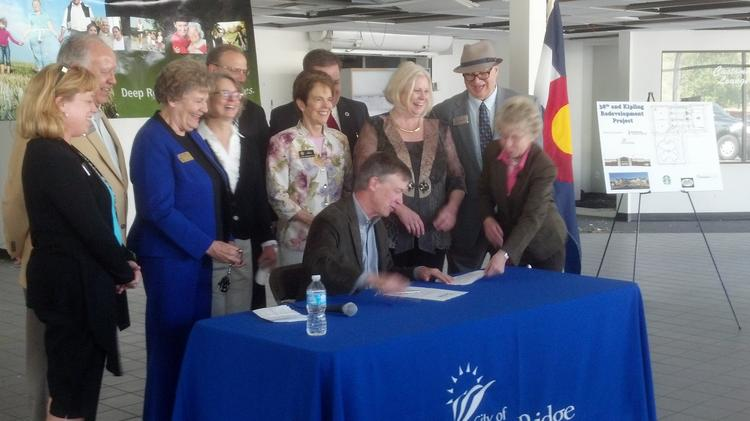 Wheat Ridge Mayor Joyce Jay (far right) helps Gov. John Hickenlooper organize his papers while he signs a brownfield-redevelopment tax credit into law on May 15. Jay spoke at that ceremony about the benefits of urban-renewal projects, and now municipal and developer groups are asking Hickenlooper to veto another bill they say will stall urban-renewal authorities.
