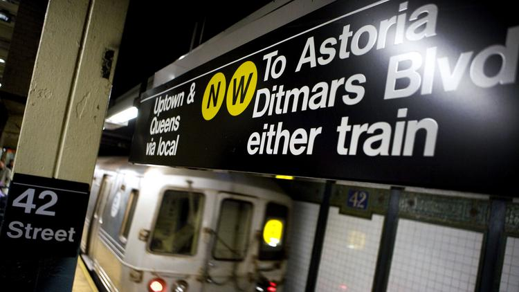 """An """"R"""" line train leaves the 42nd Street subway station in New York. Massimo Vignelli played a major role in designing the signage system the subway still uses today."""