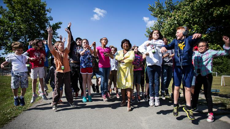 Freda Hicks, pictured center, principal at Perry Harrison Elementary School, Pittsboro, stands with Ms. Tompkins' fourth grade class as they jump with enthusiasm over digital learning on May 22. Tompkins 4th grade classroom uses the Walking Classroom model as a teacher-initiated, in-school fitness and obesity intervention that improves health literacy and builds core content knowledge while addressing different learning styles.