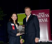 Beppy Owen of Akerman Senterfitt accepts a 2013 Women To Watch award for Megan Costa DeVault who was unable to attend.