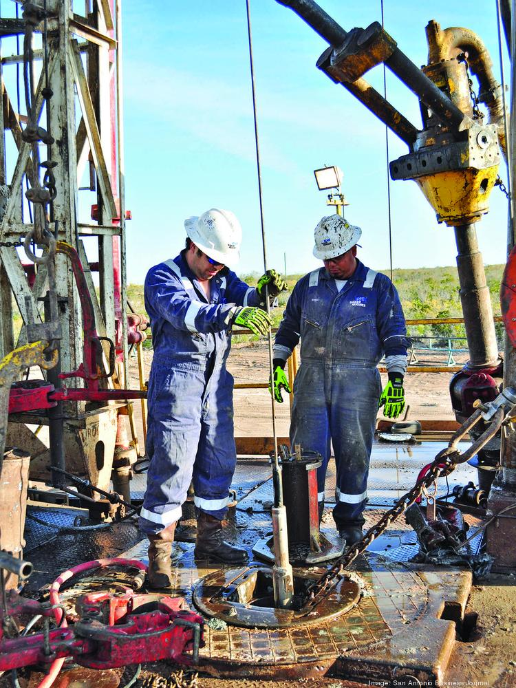 Employees of oilfield services giant Baker Hughes work at a drilling site. The Eagle Ford has four of the state's top oil-producting counties, according to new state data.