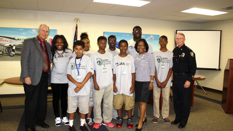 The JAXEX High Achievers stand with JAA Executive Director Steve Grossman (far left), Jacksonville Sheriff John Rutherford (far right) and JAXEX Airport Manager Tiffany Gillem (front row, striped shirt) at their graduation. This was the inaugural group for the High Achievers Program.