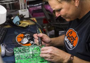 Geek Squad employee Gayle Jessie repairs a controller board in the TV reclamation area at Geek Squad City in Hillview, Ky.