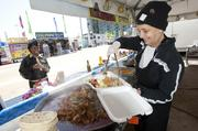 Tina Jones with the Greek Flame Foods booth at the Chow Wagon served up a dish of chicken goodness for Quiana McGrew, a petty officer in the U.S. Navy.
