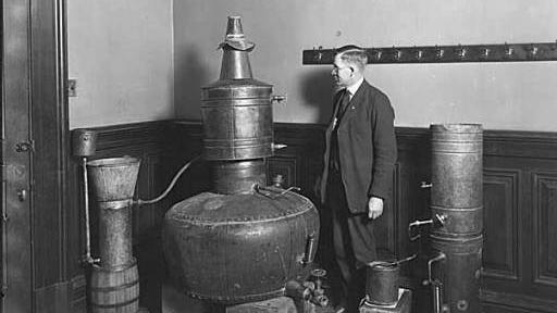 A federal agent in Seattle inspects a still confiscated from bootleggers in 1921. Many Seattleites celebrated the end of Prohibition, as they are also doing in the run-up to state-licensed marijuana sales.
