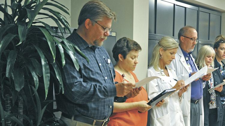 (From left) Inpatient nurse managers Dan Poupard, Sharon Monical, Emily Hazelton and Tom Oreskovich; and manager of environmental services Diana Moore discuss patient volumes with Saint Louis University Hospital administrators.