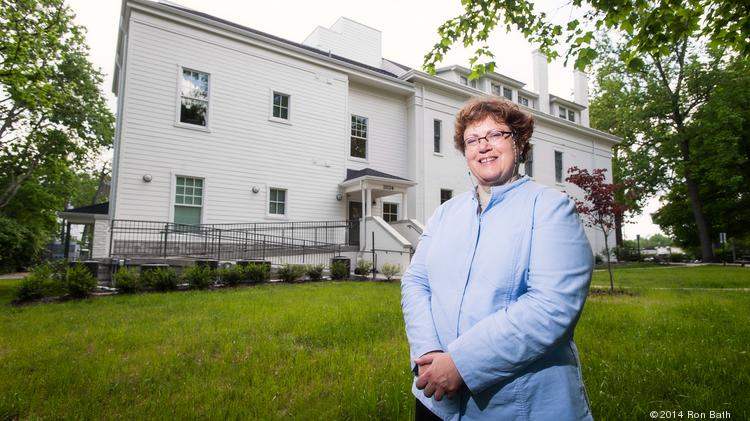 Cathy Hinko, Executive Director for the Metropolitan Housing Coalition, is an advocate for affordable housing like that provided at The Woodbourne House behind her in the Highlands.  There are 11 apartments of rent-subsidized housing for the elderly provided there.
