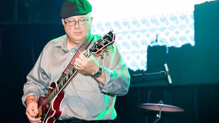 Bob Corcoran of Bad Idea, the band made up of employees of Merrimack Pharmaceuticals, in the Battle of the Biotech Bands. The band also consisted of Alia Albeer (Lead Vocals); Ben Olds (Lead Vocals); Washington Alves (Drums); Sergio Iadevaia (Guitar); Tim Munroe (Bass Guitar); Marsha Marande (Keyboards); Mel Maisel (Saxophone & Back Up Vocals) ; and Hannah Hudson (Mandolin & Back Up Vocals).