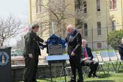 Michael Reynolds, Midwest Region director of the National Park Service (left) and Robert Beller, director of the Milwaukee VA Medical Center, unveil the plaque dedicating the landmark status.