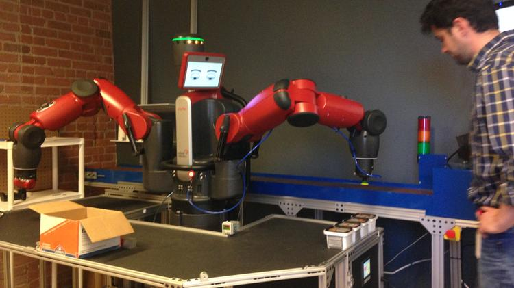 A Rethink Robotics employee watches as Baxter the manufacturing robot performs a task at the company's headquarters in Boston.