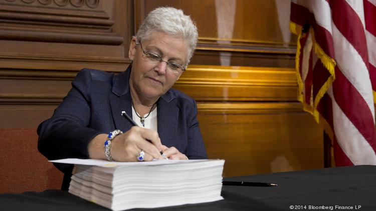 EPA Administrator Gina McCarthy signs her agency's proposed regulation requiring a 30 percent cut in carbon emissions from existing U.S. power plants.