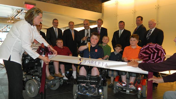 Nolan Willis, a 12-year-old with Duchenne's muscular dystropy, cut the ribbon in a celebration of the new office and lab space at 215 First Street for Sarepta Therapeutics.