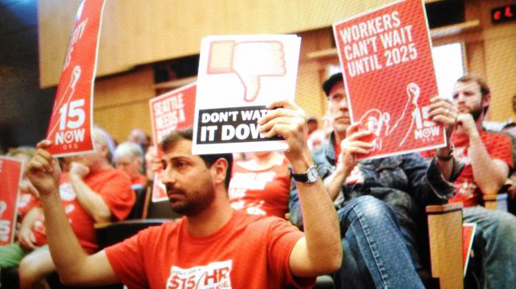 Backers of a $15 minimum wage at Seattle City Council meeting. A franchise group plans to sue the city for a minimum wage plan it says discriminates against franchises.