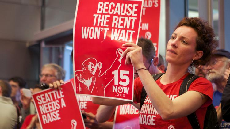 """A """"15 Now"""" supporter holds a sign during a Seattle City Council meeting in which the council voted to raise the minimum wage in Seattle, Monday June 2, 2014."""
