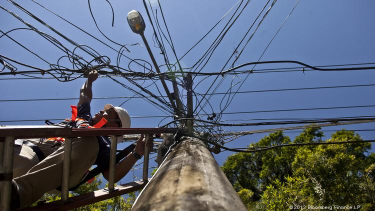 A worker installs cables on an electricity pole.