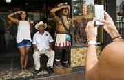 A tourist poses for a picture with a man smoking a cigar in front of a shop on Calle 8, or Eighth Street, in the Little Havana district of Miami.