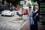 Two men stand near a sign welcoming people to Calle 8, or Eighth Street, in the Little Havana district of Miami.