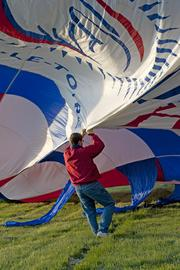 A crew member pulled on a balloon to help it inflate.