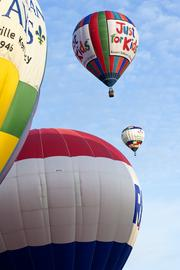 The juxtaposition of hot-air balloons taking flight in a race makes for an inviting, colorful scene.
