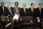 Resident Gabriel Iglesias Roman sits on a bench in front a mural of American Nations Presidents, including Belize, Peru and Granada, who attended the First Summit of the Americas in 1994, at Domino Park on Calle 8, or Eighth Street, in the Little Havana district of Miami.