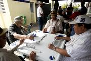 Men play a game of dominos at Domino Park on Calle 8, or Eighth Street, in the Little Havana district of Miami.