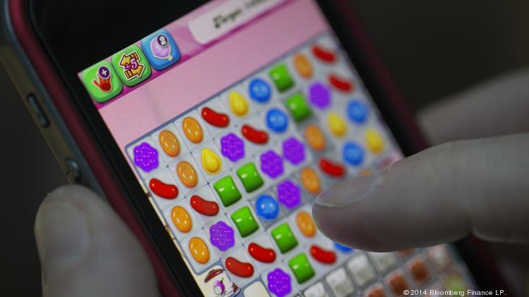 "A user plays the ""Candy Crush Saga"" puzzle game on an Apple iPhone 5."