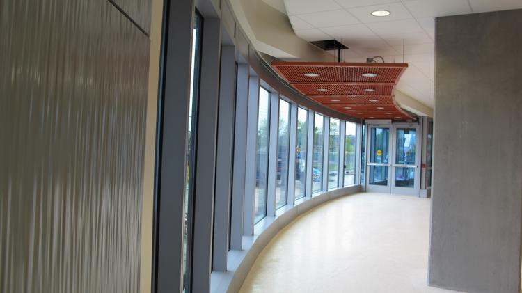 Inside and out, the School of Freshwater Sciences plays on its watery inspiration, evoking blue dripping lines (left) and wave-like curves, seen in this lobby hall.