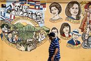 A man walks by a mural with pictures of Carlos Gardel, Selena, Rocio Durcal and Libertad Lamarque on Calle 8, or Eighth Street, in the Little Havana district of Miami.